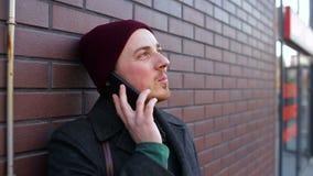 Ung ensam man som talar på telefonen nära tegelstenväggen i staden lager videofilmer