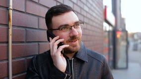 Ung ensam man som talar på telefonen nära tegelstenväggen i staden arkivfilmer