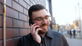 Ung ensam man som talar på telefonen nära tegelstenväggen i staden stock video