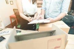 Ung entreprenör som kontrollerar dokumentet med marknadsföringslaget Fotografering för Bildbyråer