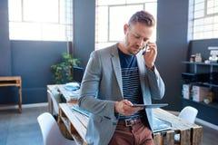 Ung entreprenör som talar på hans mobiltelefon och använder en minnestavla royaltyfria foton