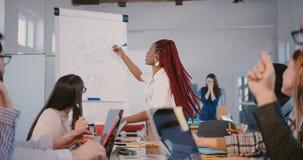 Ung erfaren positiv kvinna för lagledare för afrikansk amerikanfinansaffär som ger riktningar till partners på kontorsseminar stock video