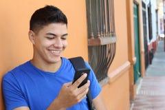 Ung etnisk man som använder en mobiltelefon royaltyfri fotografi