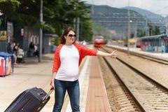 Ung europeisk gravid kvinna med tungt bagage som försöker att stoppa drevet på järnvägsstationen för att resa på den soliga dagen arkivbilder