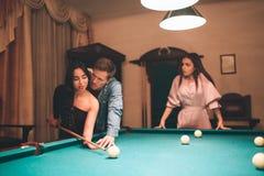 Ung europeisk kvinnablick på par som spelar billiard Henne som är jelaous Modellen är sinnessjuk Kvinna för hjälp för ung man asi royaltyfri foto