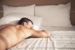 Ung europeisk man för stående som sover i säng arkivfoto