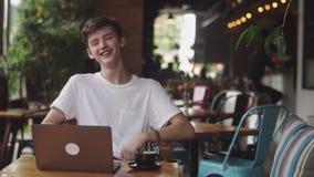 Ung europeisk man som inomhus ler och skrattar i kafét, freelanceren och bloggeren som har rolig pratstund, modern kommunikation arkivfilmer