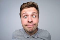 Ung europeisk man som ser på näsa Hans ögon är den skelade blicken arkivfoton