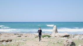 Ung färdig caucasian man som kör på stranden in mot kameran Hav med starka vågor på backgounden lager videofilmer