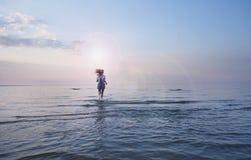 Ung färdig kvinna som joggar på en strand i bikini i Bali Köra som är utomhus-, eller utarbeta Färdig kvinna som kör på den tomma royaltyfri foto