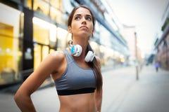 Ung färdig kvinna som lyssnar till musik och utarbetar, genom att köra royaltyfria bilder