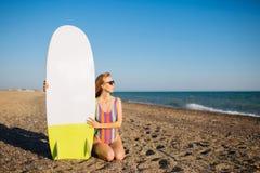 Ung färdig surfareflicka på stranden med ett bränningbräde royaltyfria foton
