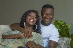 Ung förälskad liggande skämtsam kel för attraktiva och lyckliga romantiska afrikansk amerikanpar på vardagsrumsoffan som tillsamm arkivfoton
