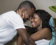 Ung förälskad liggande skämtsam kel för attraktiva och lyckliga romantiska afrikansk amerikanpar på vardagsrumsoffan som tillsamm royaltyfri foto