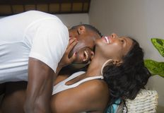 Ung förälskad liggande skämtsam kel för attraktiva och lyckliga romantiska afrikansk amerikanpar på vardagsrumsoffan som tillsamm royaltyfri fotografi
