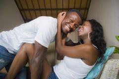 Ung förälskad liggande skämtsam kel för attraktiva och lyckliga romantiska afro amerikanska par på vardagsrumsoffan som tillsamma royaltyfri fotografi
