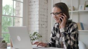 Ung företagsägarekvinna som arbetar med bärbara datorn, talande hållaretelefon i inrikesdepartementet stock video