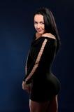 Ung förförisk kvinna i svart kappa arkivbild
