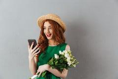 Ung förvånad kvinna för rödhårig man med att prata för blommor royaltyfri fotografi