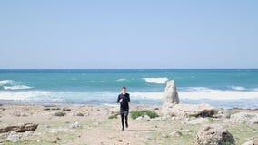 Ung f?rdig caucasian man som k?r p? stranden in mot kameran Hav med starka vågor på bakgrunden l?ngsam r?relse stock video