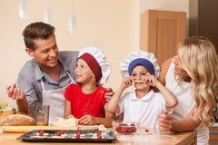 Ung fader och moder som tillsammans lagar mat Arkivbilder
