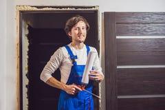 Ung faktotum som installerar dörren med ett beslagskum i ett rum arkivfoton