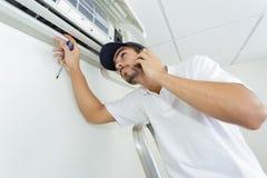 Ung faktotum som reparerar det betingande systemet för luft som kallar för hjälp Arkivbilder