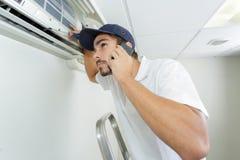 Ung faktotum som reparerar det betingande systemet för luft som kallar för hjälp Royaltyfria Bilder