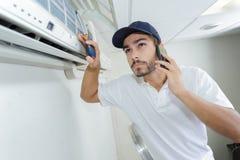Ung faktotum som reparerar det betingande systemet för luft som kallar för hjälp Royaltyfri Bild