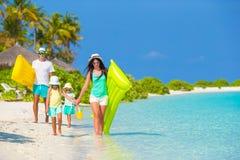 Ung familj av fyra på strandsemester Royaltyfria Foton