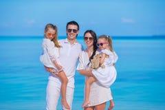 Ung familj av fyra på strandsemester Arkivbild