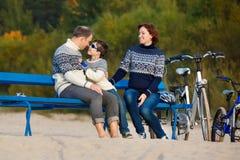 Ung familj av tre som har att vila på bänk under deras cykelridning på stranden arkivfoto
