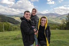 Ung familj: farsa, mamma och dotter under en semester i bergen arkivbild