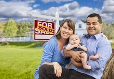 Ung familj framme av Sold Real Estate tecknet och huset Arkivfoton