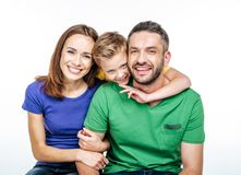Ung familj i färgrika t-skjortor som har roligt och ser kameran royaltyfri foto