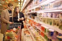 Ung familj i livsmedelsbutik arkivfoton