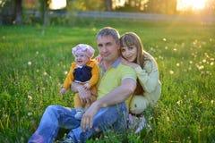Ung familj i sommarfältet Arkivbild