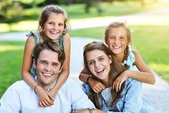 Ung familj med barn som har gyckel i natur royaltyfria foton