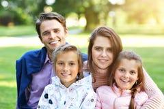 Ung familj med barn som har gyckel i natur arkivfoton