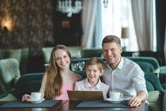 Ung familj med barnet inomhus Arkivbild