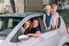 Ung familj med deras barn i en familjebil arkivfoton