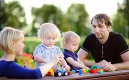 Ung familj med deras barn som spelar med leksaker Royaltyfria Foton