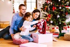 Ung familj med dottern på julgranen hemma arkivfoton