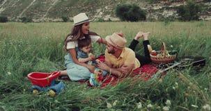 Ung familj med en behandla som ett barnpojke som tillsammans spenderar fantastisk tid på picknicken som spelar med de lager videofilmer