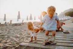 Ung familj med litet barnbarn som har gyckel p? stranden p? sommarferie royaltyfria bilder