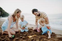 Ung familj med litet barnbarn som spelar med sand p? stranden p? sommarferie royaltyfri bild