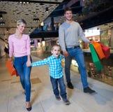 Ung familj med shoppingpåsar arkivfoto