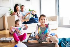 Ung familj med två barn som packar för ferie arkivbilder