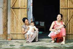 ung familj med ungar och farmodern framme av deras hem royaltyfria bilder