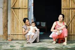 ung familj med ungar och farmodern framme av deras hem royaltyfri bild